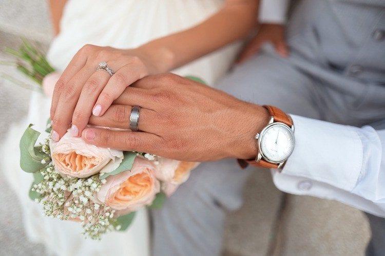 Bride and Groom's Hands on Wedding Bouquet