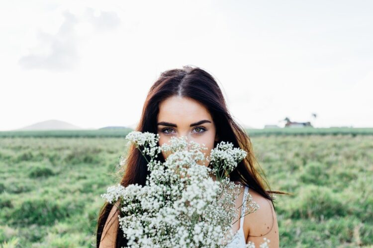 How to Forgive Someone Who Keeps Hurting You   Image shows a woman holding a bunch of flowers in front of her face.