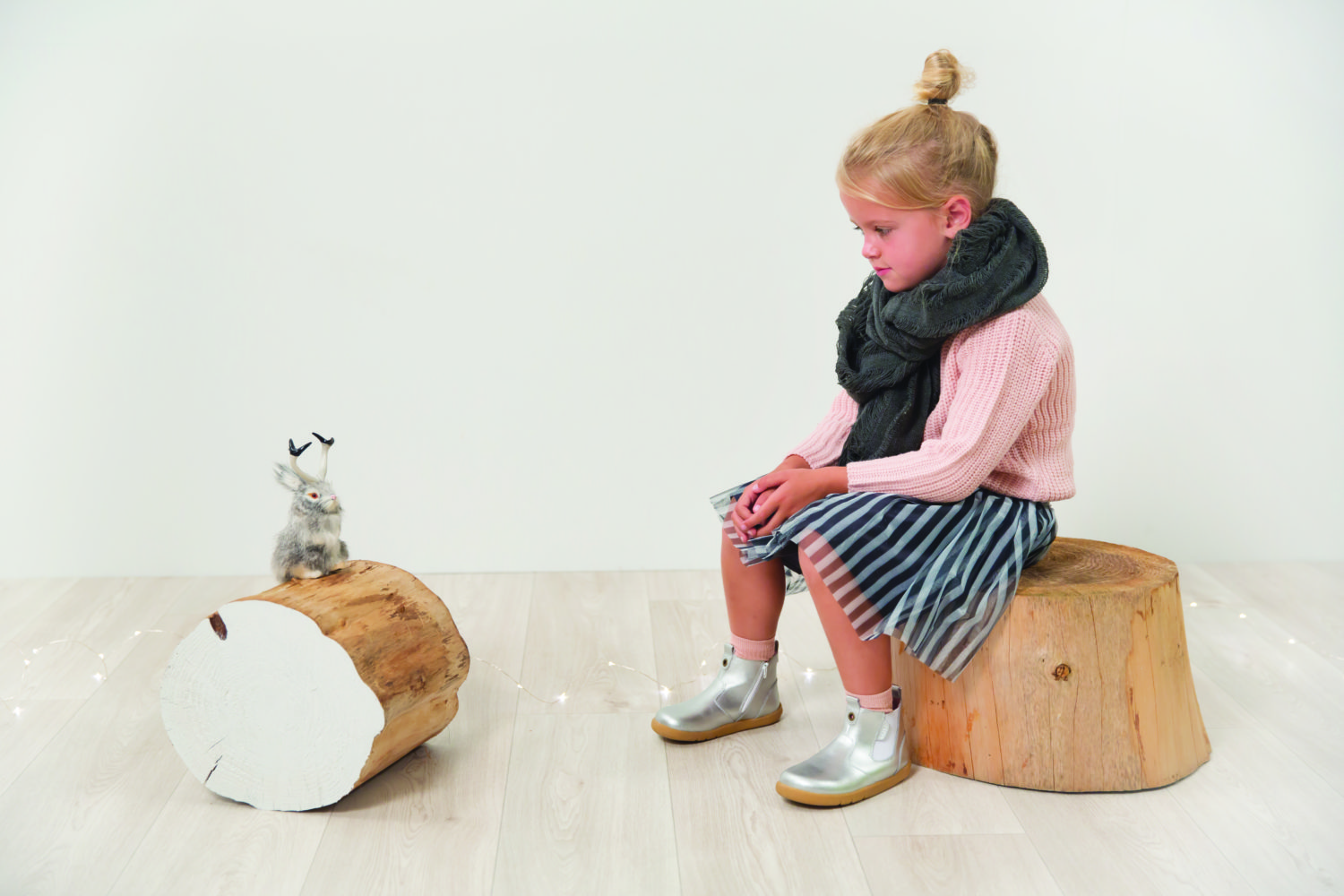 Little girl sitting on a log looking fed up.