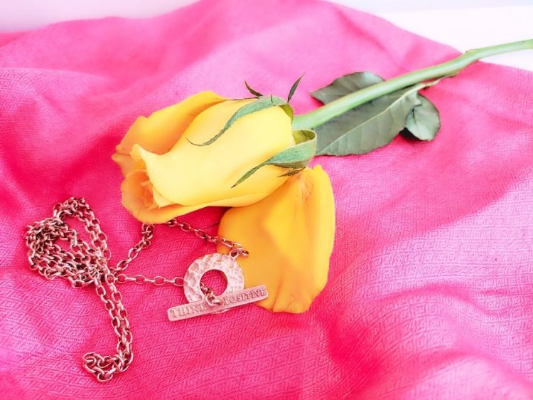 Think Positive chain with yellow rose on a coral background.
