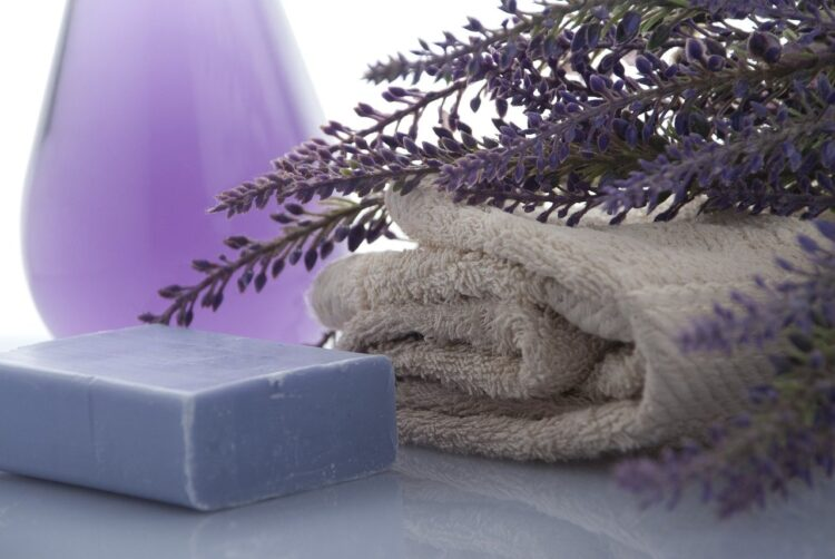 Folded towel with a bar of soap and a purple vase behind it.