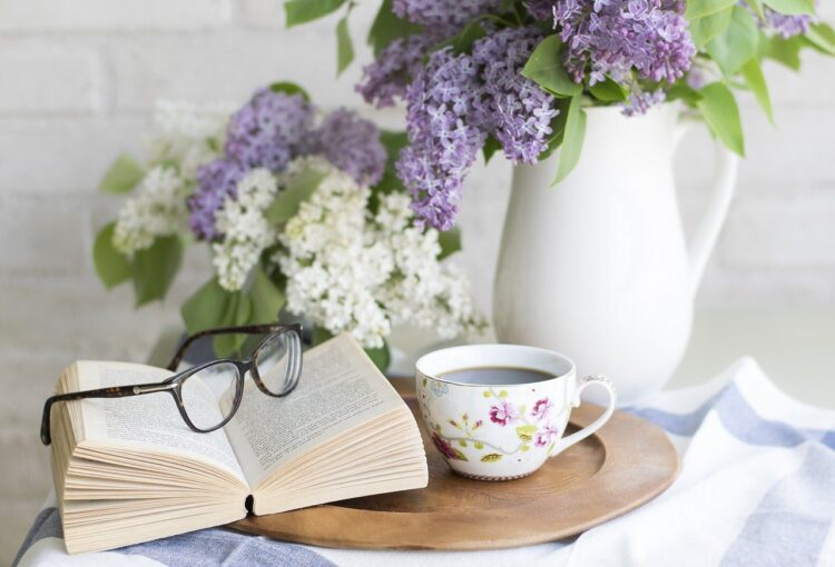 Sunday self care | Image shows an open book beside a cup of coffee and a white jug holding purple flowers.