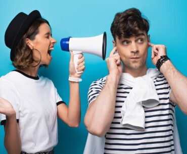 Ear Wax Removal Tool - Woman Shouting at Man With Megaphone