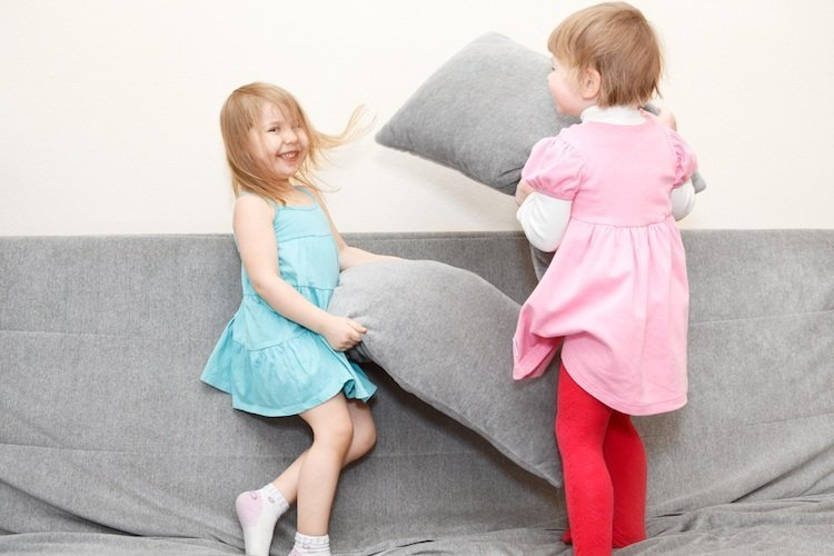 Children Play Fighting With Cushions