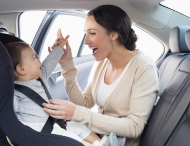 Child Seat Laws UK - Mother Strapping Child Into Car