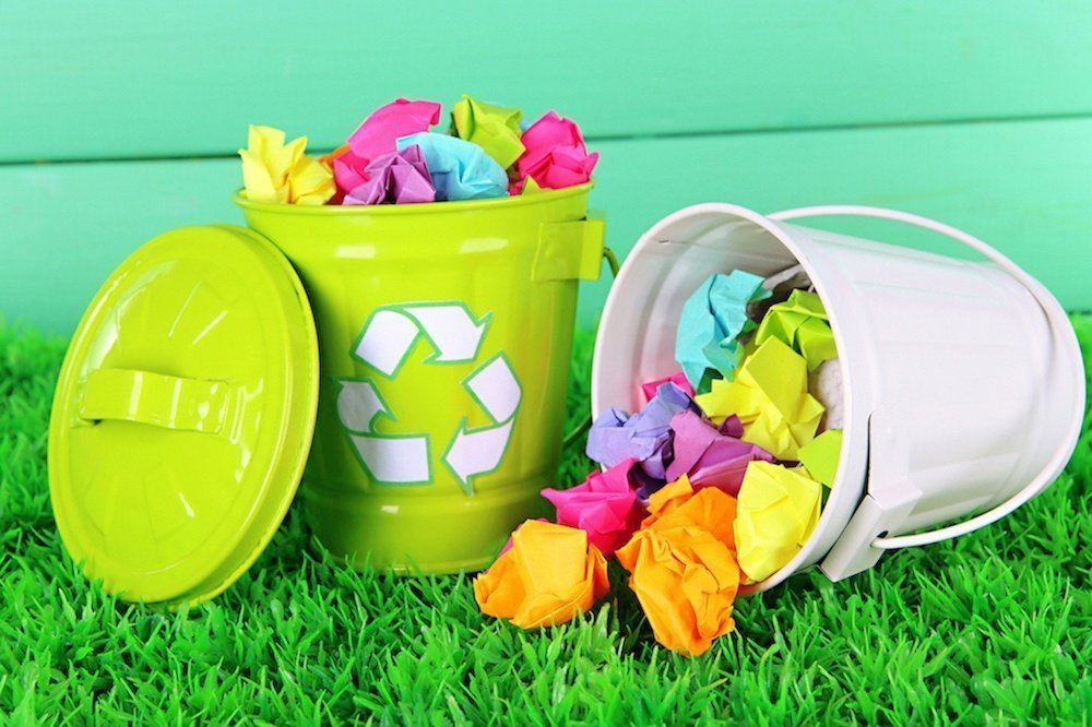Image shows a recycling bin full of colourful paper.