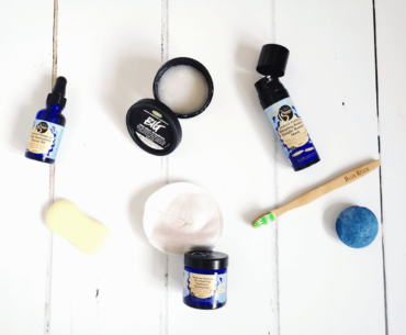 Sustainable Go Green Products for the Bathroom Including Skincare, a Bar of Soap, and a Bamboo Toothbrush