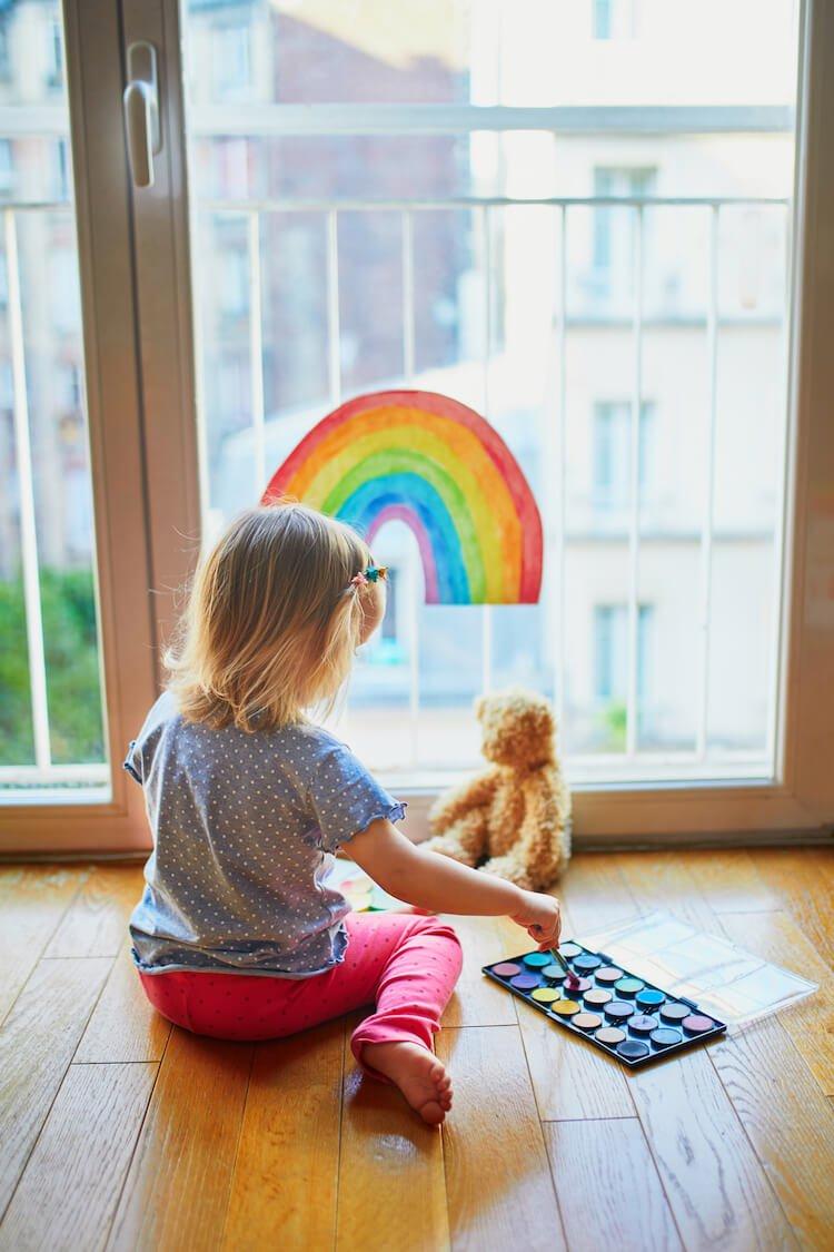 Child Painting Rainbow on Window