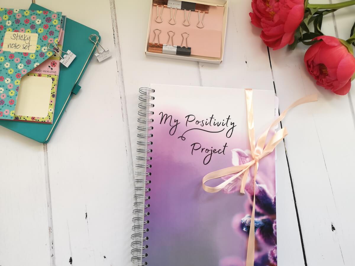 Mindful Journaling | How to Write in a Journal | Image shows a journal on a desk, with some pretty stationery and peonies.