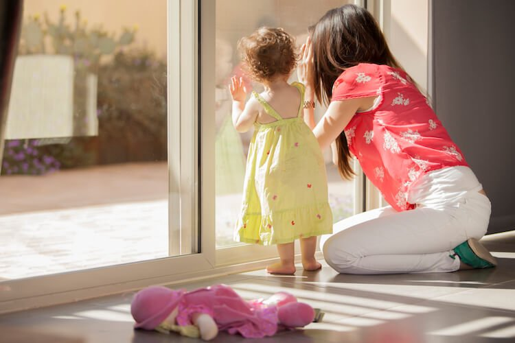 Mother Looking Out of Window With Toddler