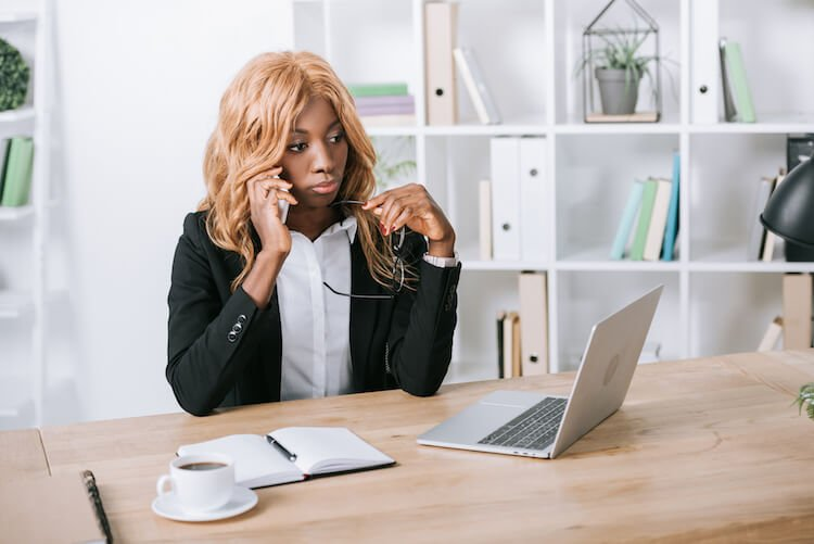 Woman on Phone in Office Looking Worried