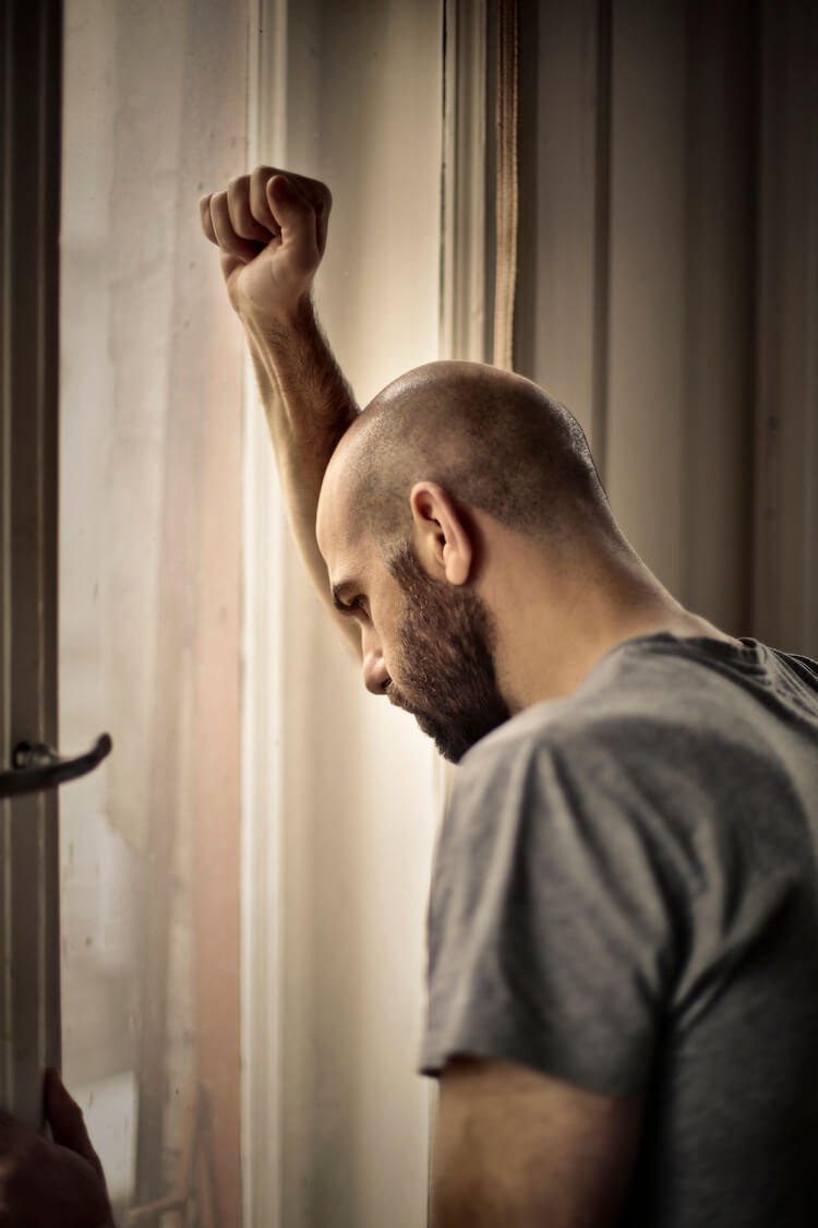 Worried Man Standing at Window