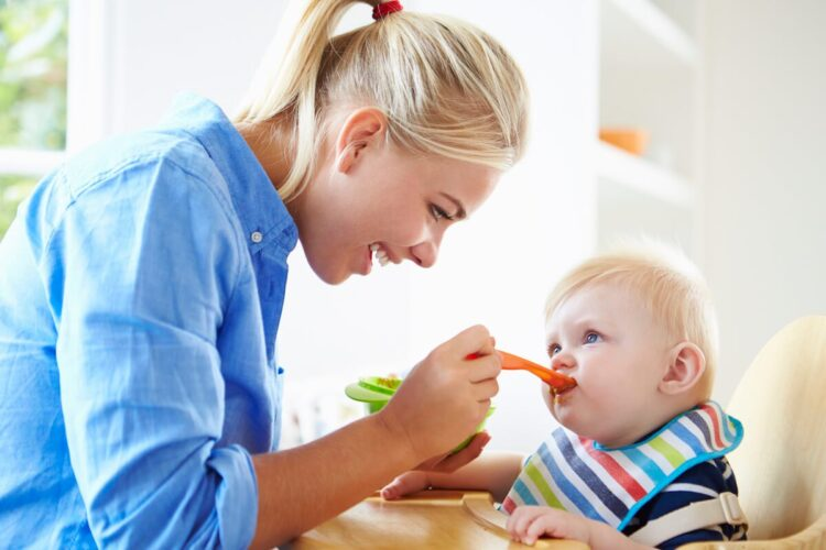 Dairy free food for babies. | Image shows a mum wearing a blue shirt, spoon-feeding her infant.