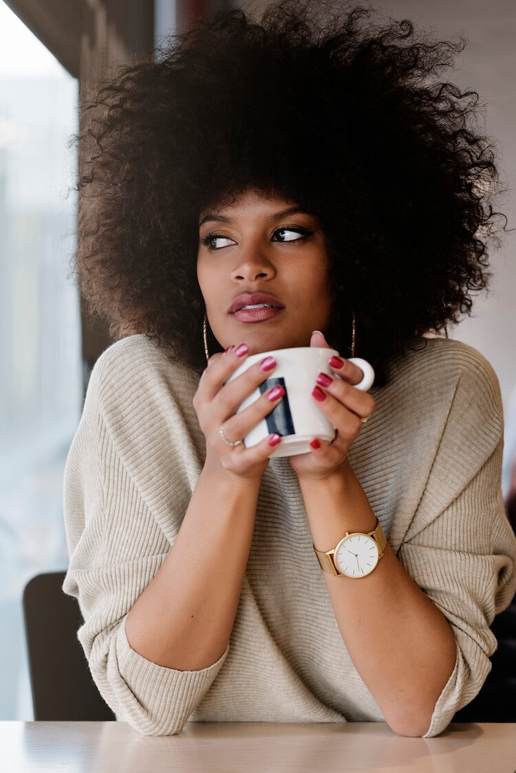 Embracing the knowledge that you are responsible for your own happiness can be empowering. Image shows a pensive woman drinking coffee.