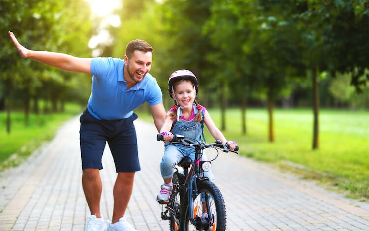 Dad Helping Daughter Learn to Ride a Bike