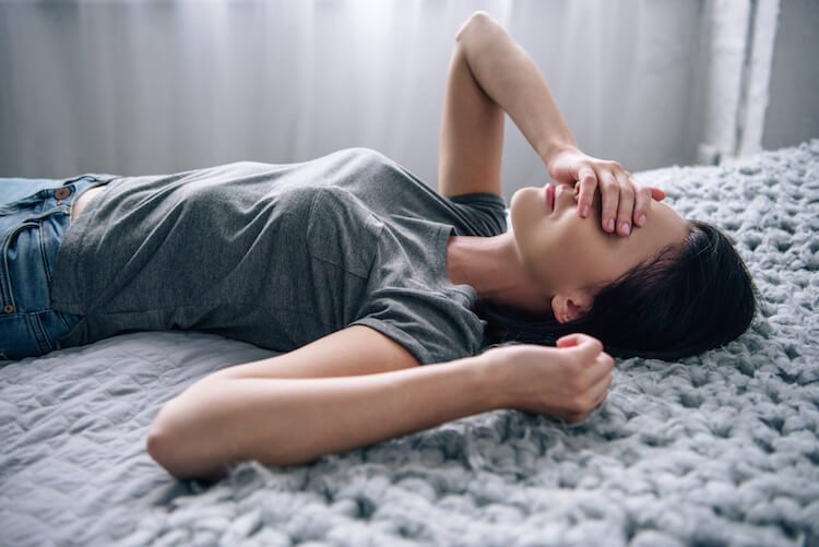 Woman Laying on Bed With Head in Hands
