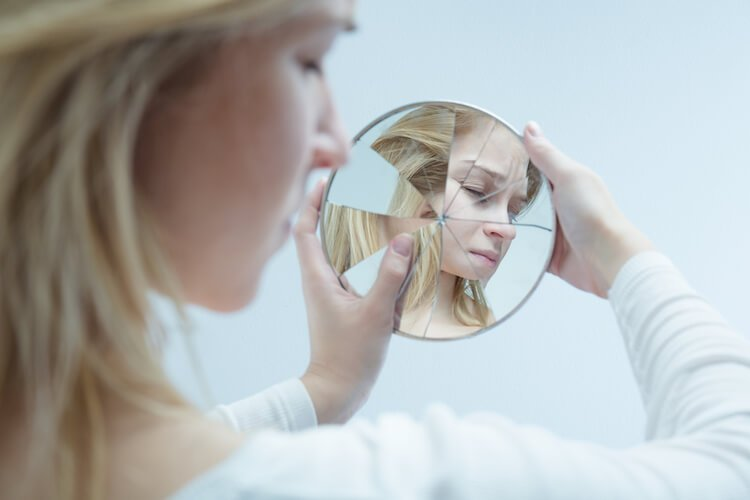 Woman Looking in Broken Mirror