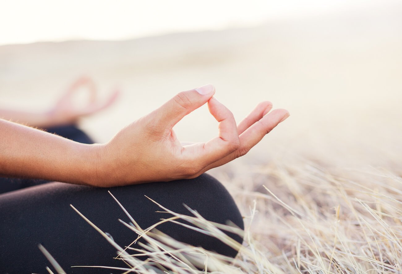 Inner child healing meditation can be useful for childhood trauma. Image shows woman sitting in a field with her finger and thumb together.