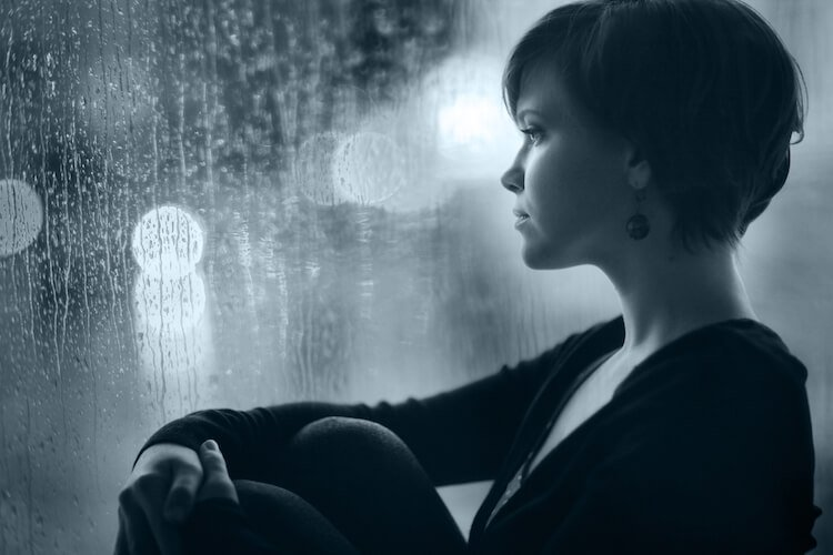 Reparenting yourself is a valuable tool for working through childhood trauma. Image shows woman sitting by a rain-spattered window.