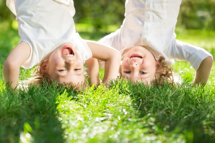Image shows two laughing children doing handstands on grass.