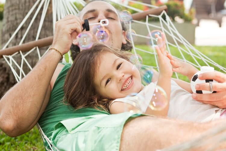 Father and daughter laying in a hammock, with dad blowing bubbles.