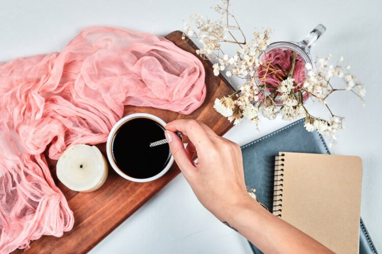 Self loving affirmations | Image shows a woman with a journal, flowers, and candle on a desk, stirring coffee.