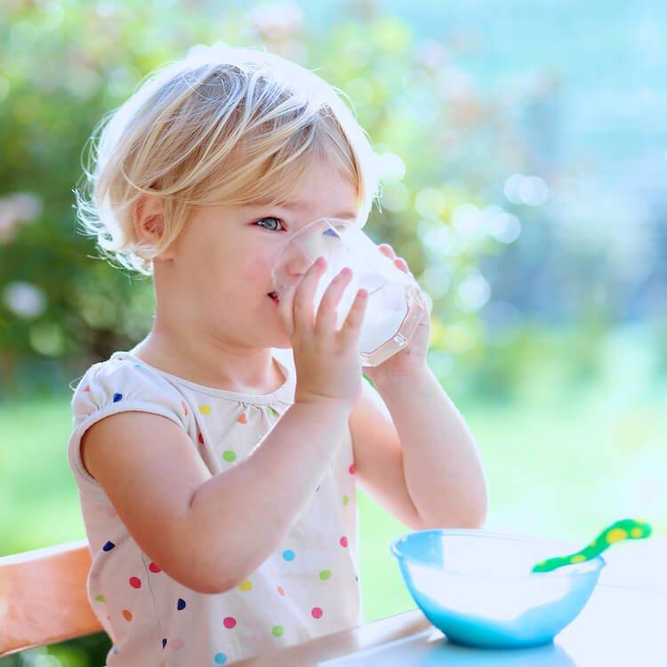 Girl drinking glass of milk.
