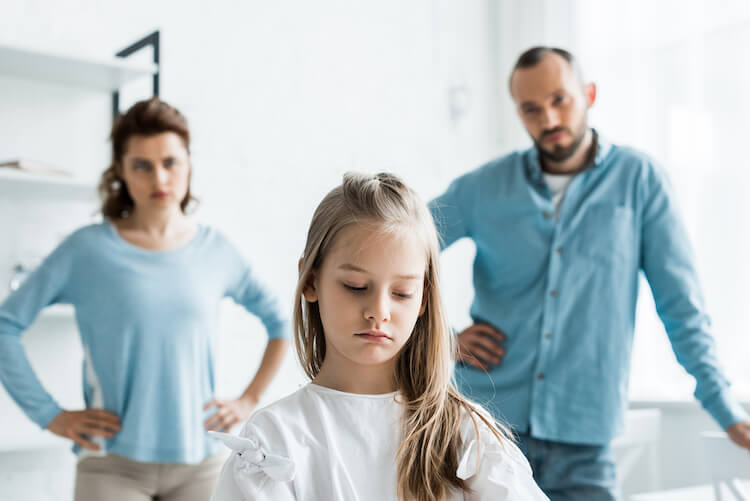 Pouting child standing in front of her parents.