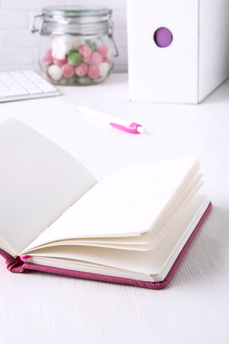 A journal open on a white desk with a pen and jar of sweets in the background.