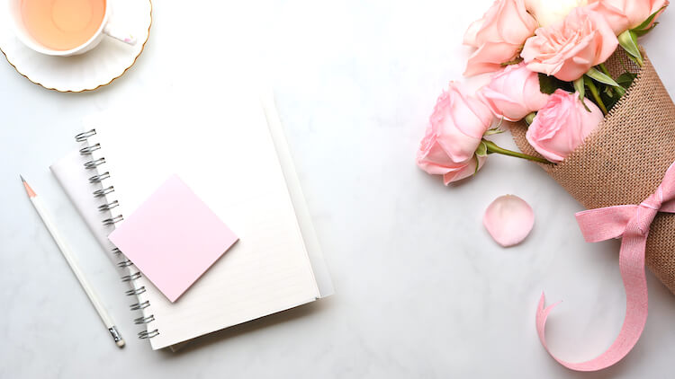 A journal with pink Post-It notes on top of it. There are some pale pink roses beside the journal and a cup of herbal tea half in shot.