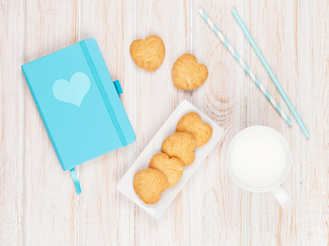 Image shows a cup of milk, some straws, some biscuits and a diary on a table.