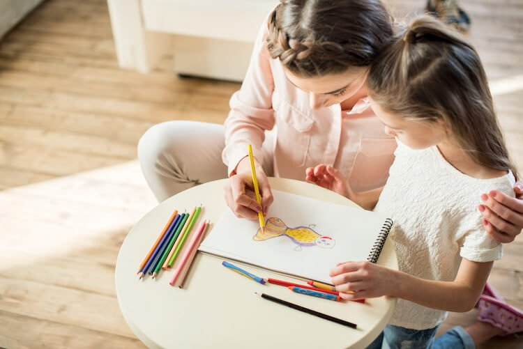 How to stop your child sulking: build connection. Image shows a mother and daughter colouring together.