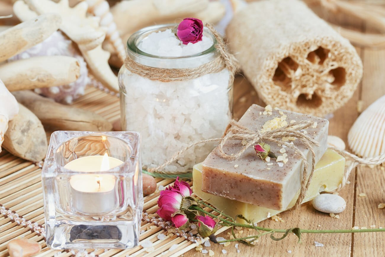 Pampering items, including a candle, exfoliating sponge, and soap.