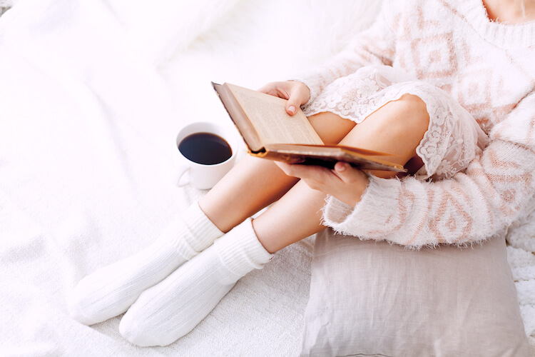 Slow living   living slowly   Image shows a woman reading on the bed. She has a cup of coffee beside her and she wears fluffy socks.