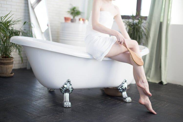 Woman sitting on edge of roll top bath exfoliating.