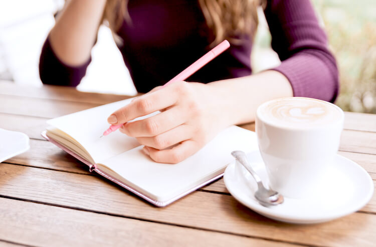 A woman is writing in a journal on a slatted wooden table top. She wears a dark purple jumper and holds a poised pen. She has a white mug beside her.
