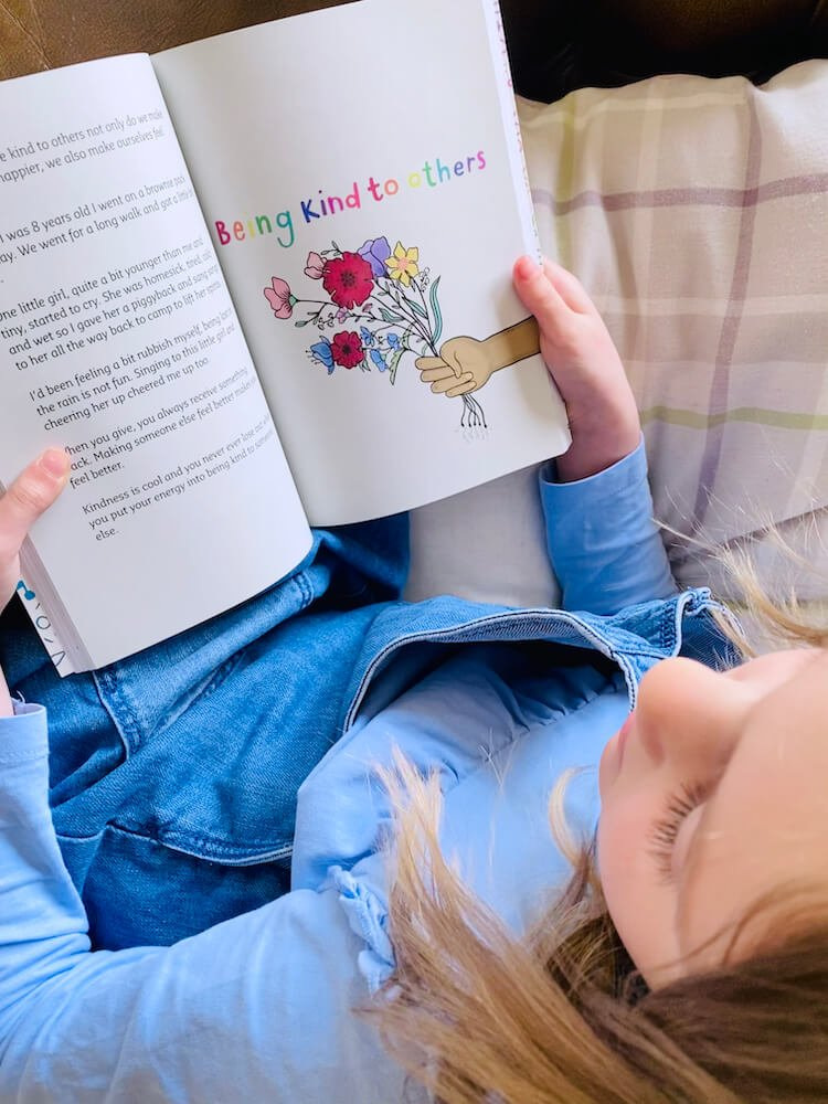 Girl reading a book about being kind to others.