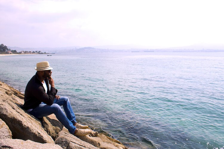 Black man looking out to sea, contemplating his core values.