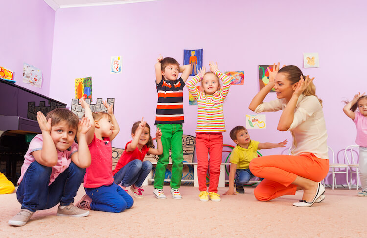 Inspirational stories for kids | Image shows a group of children listening and interacting with a teach telling a story.