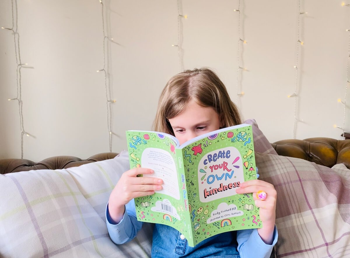 Kids kindness quotes. Image shows girl reading a book about kindness.