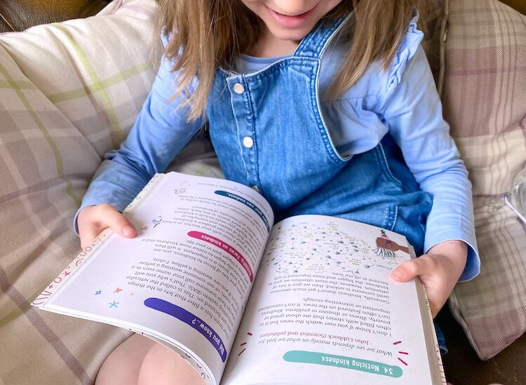 Noticing kindness. Image shows a girl reading a book about kindness.