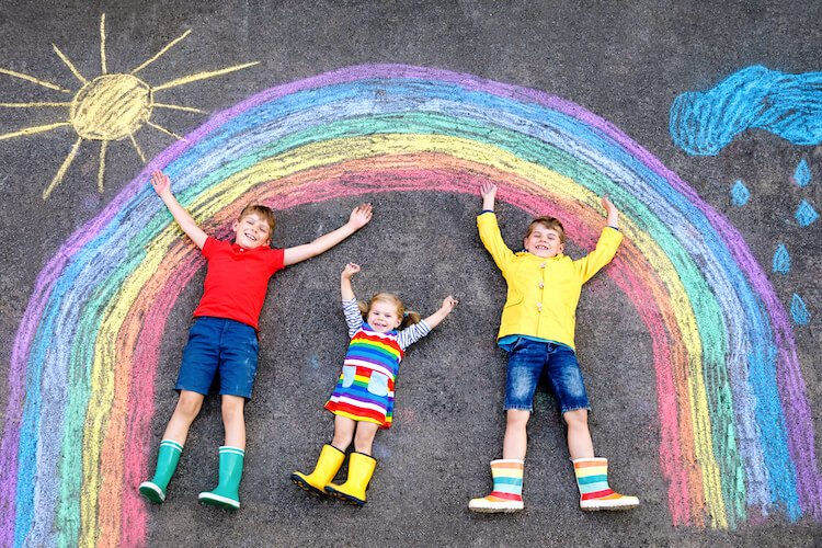 A chalk rainbow drawn on a playground with kids posing under its arch.