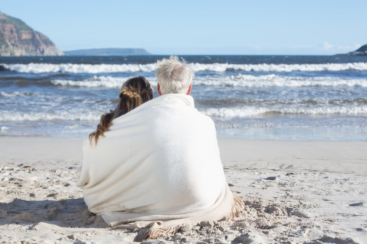Couple wrapped in a blanket looking out to sea.