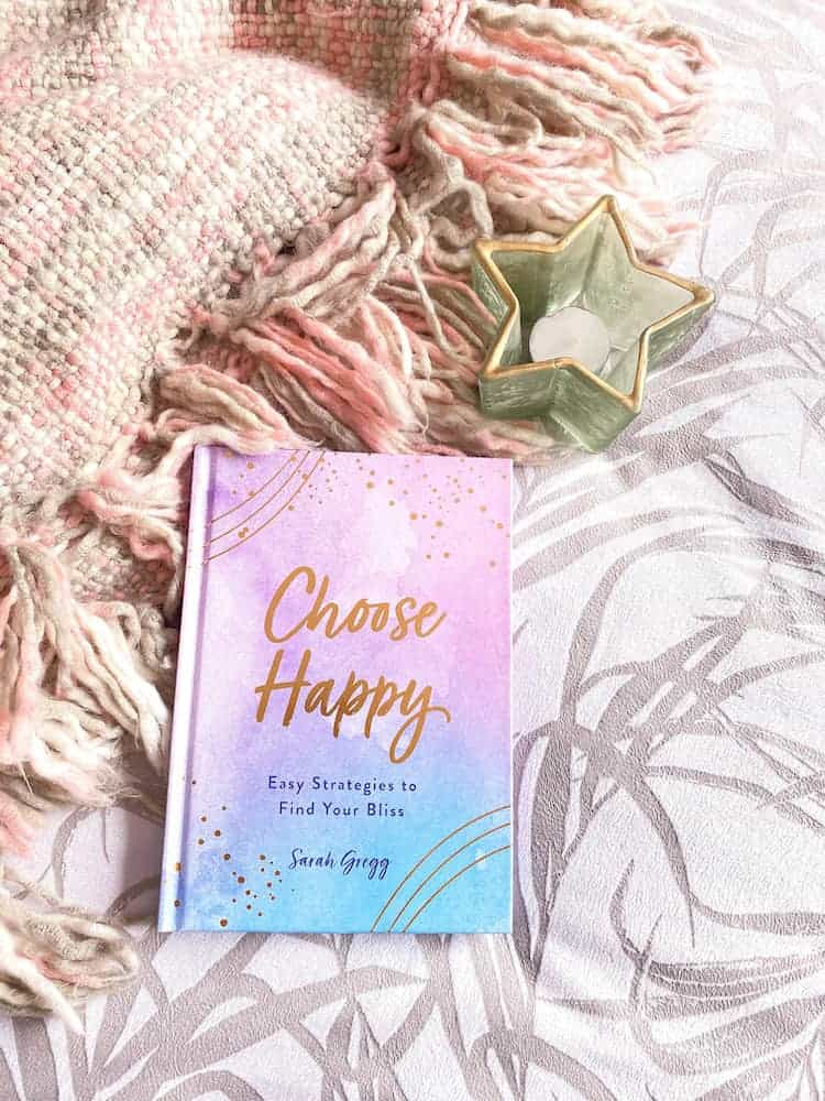 Happy vs content. Image shows a book called Choose Happy on a pink and grey blanket with a green star-shaped candle beside it.