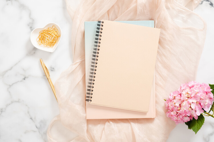 Image shows a journal lying on a peach scarf next to some pink flowers.