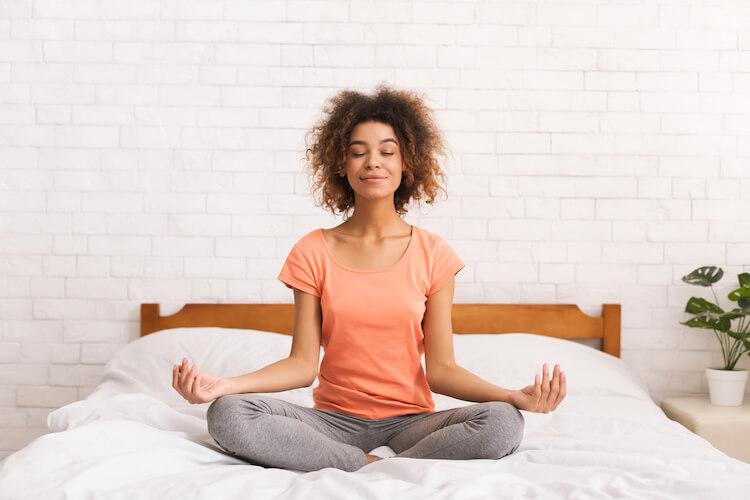 Manifesting positivity   Woman meditating on bed.