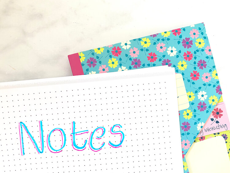 The word 'notes' written in blue pen with a magenta shadow. There's a colourful, flowery notepad in the background.