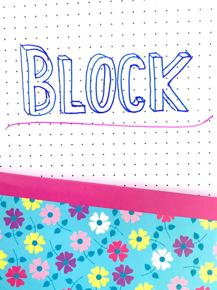 The word 'block' written in block writing and underlined in pink pen. There's a flowery notebook in the background.