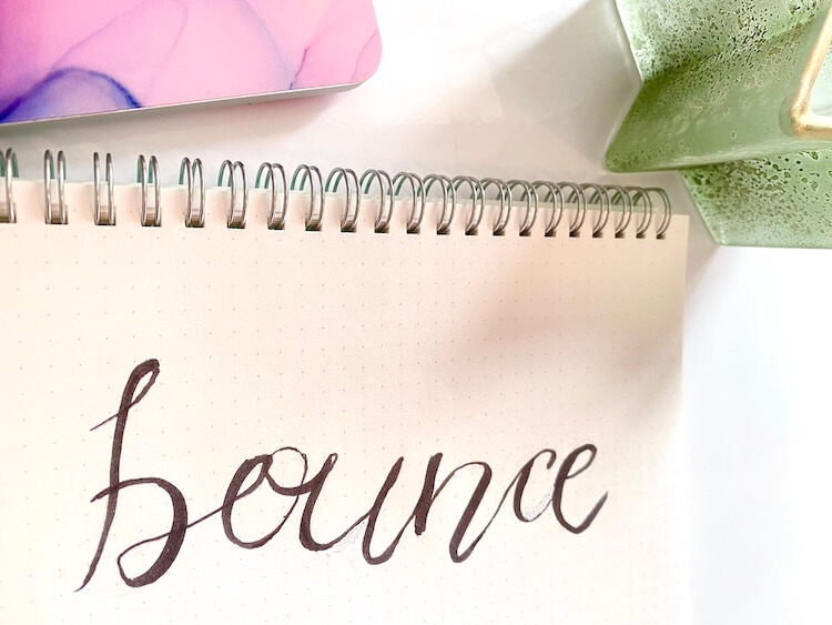 The word 'bounce' written in black bounce brush font, with a marbled pink background.