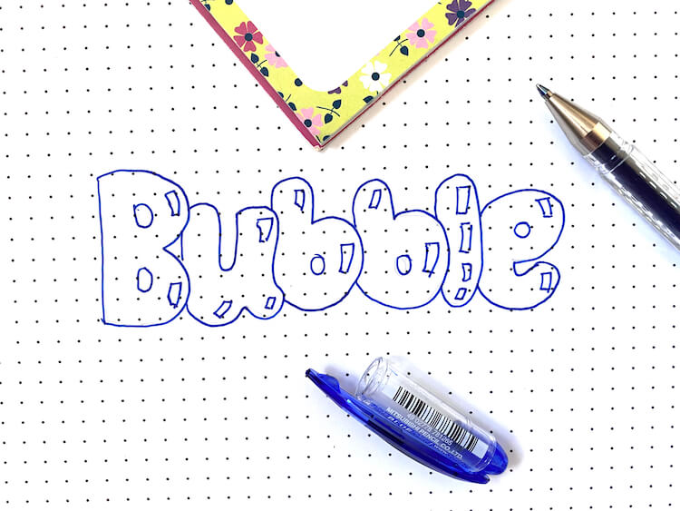 The word 'bubble' written in blue bubble font. The blue pen is open next to the writing and there's a flowery notebook in the background.